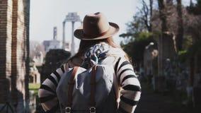 Kamera poruszająca wokoło młodej turystycznej kobiety stoi przy forum Rzym ruiny w Włochy w kapeluszu z plecakiem i rękami na bio zdjęcie wideo