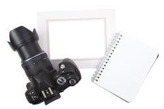 Kamera und Rahmen mit Notizblock Stockfotografie