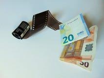 Kamerafilm som vänder in i pengar | stockphotographybegrepp Arkivbild