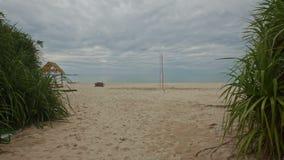 Kameraflyttningar vid litet gömma i handflatan för att sandpappra stranden med netto volleyboll stock video