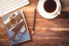 Kameragläser und -Teetasse auf altem hölzernem Hintergrund Lizenzfreie Stockbilder