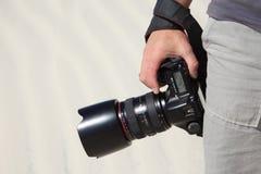 kamerahanden rymmer fotoet royaltyfri fotografi