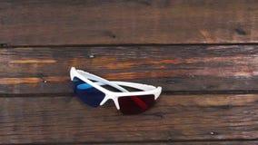 Kamerakran, hochschiebend, alte Gläser 3d mit den blau-roten Linsen, die auf einem schönen, alten Holztisch mit Kopienraum liegen stock video