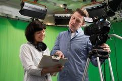 Kameraman And Floor Manager i televisionstudio Fotografering för Bildbyråer