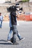 Kameraman går med den stora kameran på skuldra Royaltyfria Foton