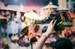 Kameraman lyfter camcorderen ovanför hans huvud, medan filma videoen royaltyfria foton