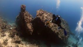 Kameramandykare som simmar djupt undervattens- i Röda havet stock video