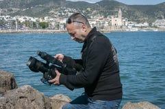 Kameramaninspelningdet fria, medan anteckna ett musikvideogem royaltyfri fotografi