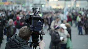 Kameramann schießt Leute auf einen gedrängten Platz.