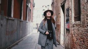 Kameran följer den attraktiva yrkesmässiga kvinnliga journalisten med kameran som promenerar den härliga gatan i Venedig, Italien stock video
