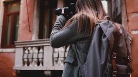 Kameran följer den härliga le turist- kvinnan som tar fotoet med den yrkesmässiga kameran i gammal Venedig gataultrarapid lager videofilmer
