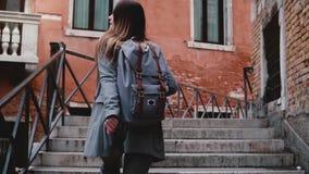 Kameran följer den härliga loppbloggerkvinnan som går med kameran på trappa i den Venedig gatan som tar en fotoultrarapid stock video