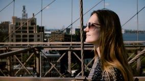 Kameran följer den härliga lyckliga europeiska brunettaffärskvinnan i stilfull solglasögon som promenerar den Brooklyn bron 4K arkivfilmer