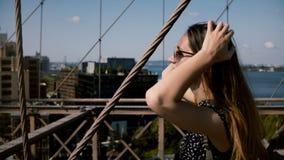 Kameran följer den härliga lyckliga europeiska flickan i tappningsolglasögon med guld- hår som promenerar den Brooklyn bron 4K stock video