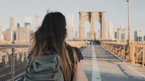 Kameran följer den unga kvinnan med ryggsäcken som promenerar den Brooklyn bron, New York på en härlig solig sommardag 4K arkivfilmer