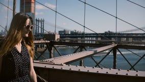 Kameran följer den unga lyckliga kvinnliga turisten med ryggsäcken i solglasögon som promenerar den Brooklyn bron som tycker om s stock video