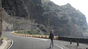 Kameran följer en kvinna på en väg med ryggsäcken som går från en tunnel in mot en klippkant ovanför havet som lyfter armar arkivfilmer