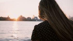 Kameran följer flickan med hår som blåser i vindkörningen in mot vattenkanten, stopp och blick på New York solnedgånghorisont 4K lager videofilmer