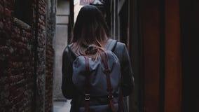 Kameran följer kvinnaturisten med ryggsäcken som promenerar den härliga mörka gamla stadsgatan i Venedig, Italien ultrarapid arkivfilmer