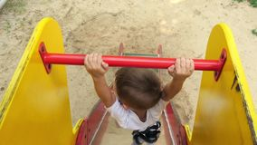 Kameran följer pojken som går ner barnens glidbana på lekplatsen Lycklig unge som in spelar på lekplatsen lager videofilmer