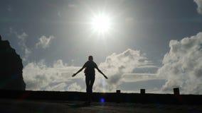 Kameran f?ljer en kvinnakontur som ut g?r fr?n tunnelen in mot solljuset Bristning av ljust ljus Lyfta armar in arkivfilmer