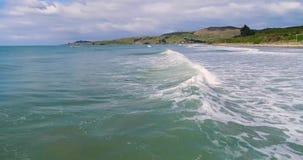 Kameran flyger över vågorna i havet mot bakgrunden av kullarna Shevelev arkivfilmer