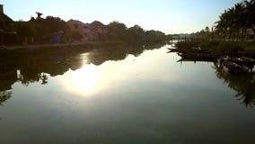 Kameran flyttar sig bak soluppgångreflexion på kanalvatten stock video