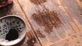 Kameran flyttar sig från från vänster till höger och tar bort små koppar som fylls med te stock video