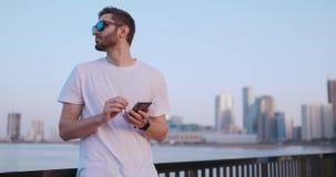 Kameran flyttar sig runt om stilig ung man, som han anv?nder hans telefon St?ende suddighet bakgrund stock video