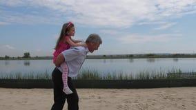 Kameran ?r i r?relse Flickan kör längs stranden med hennes sondotter på henne baksida flickan little jublar 4K saktar lager videofilmer