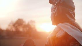 Kameran vippar på upp på liten flicka i den roliga plana pilot- dräkten som ser solnedgång med fridsam avkopplad ögonultrarapid stock video