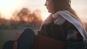 Kameran vippar på upp på nätt liten flicka i rolig plan pilot- dräkt på härlig solnedgång med fridsam ögonultrarapid arkivfilmer