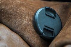 Kameraobjektiv-Abdeckhaube, die auf Kamera-Tasche liegt lizenzfreies stockfoto