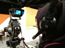 Kameraperson fungeringskameraTV-sändning i televisionstudio arkivbild