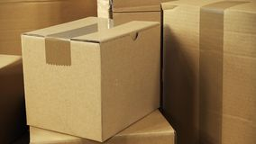 Kamerarotation över bruna lådaaskjordlotter som staplas på träkontorsskrivbordet som är klart för sändning eller levereras precis arkivfilmer