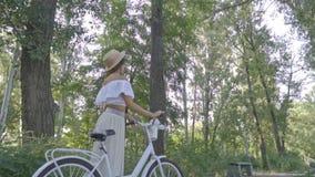 Kamerarullen på en spenslig brunett i en vit kjol, en blus och en halmtäckt hatt som står i mitt av en parkera med stock video