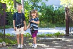Kameras des kleinen Jungen und einer Weinlese des Esprits zwei des kleinen Mädchens, die zu stehen Stockfotografie