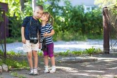 Kameras des kleinen Jungen und einer Weinlese des Esprits zwei des kleinen Mädchens, die zu stehen Lizenzfreie Stockfotos