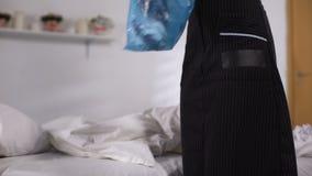 Kamermeisje die afval van bed in ochtend na partij verzamelen, die de dienst schoonmaken stock footage