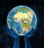 Kameroen op aarde in handen Stock Foto's