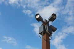 Kameror för CCTV-säkerhet tre mot på himlen Arkivfoto