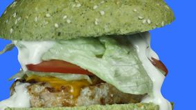 Kamery odgórny wybuch hamburger z zieloną babeczką i faszerujący pasztecik pomidory i cebule ikrzy się na zbiory wideo