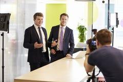Kamerzysta i dwa biznesmena robi korporacyjnemu wideo obraz royalty free