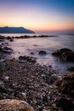 Kamień i silky fala przy zmierzchem - natury tło Zdjęcia Stock