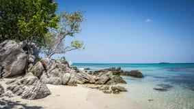 Kamień w plaży z piaskiem i wodnym błękicie z zielonym drzewem na stronie w karimun jawy wyspie zdjęcie royalty free
