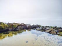 Kamieniści brzegowi igrania ocean rozjaśniają niebo z zamazanym słońcem w wysokiej wilgotności zdjęcie stock