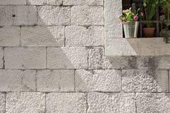 Kamieni bloków ściana z szczegółem kwiat dekorował okno zdjęcie stock