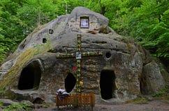 Kamieni kroków prowadzenie stara jama w górze w lesie z zielonymi drzewami obraz stock