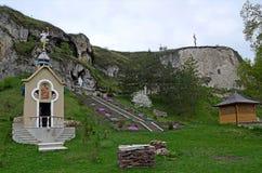 Kamieni kroków prowadzenie stara jama w górze w lesie z zielonymi drzewami obrazy royalty free