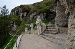 Kamieni kroków prowadzenie stara jama w górze w lesie z zielonymi drzewami zdjęcie royalty free